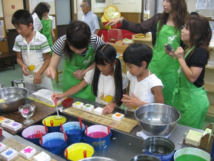 Local children making wax candles - photo by Rob McFarland